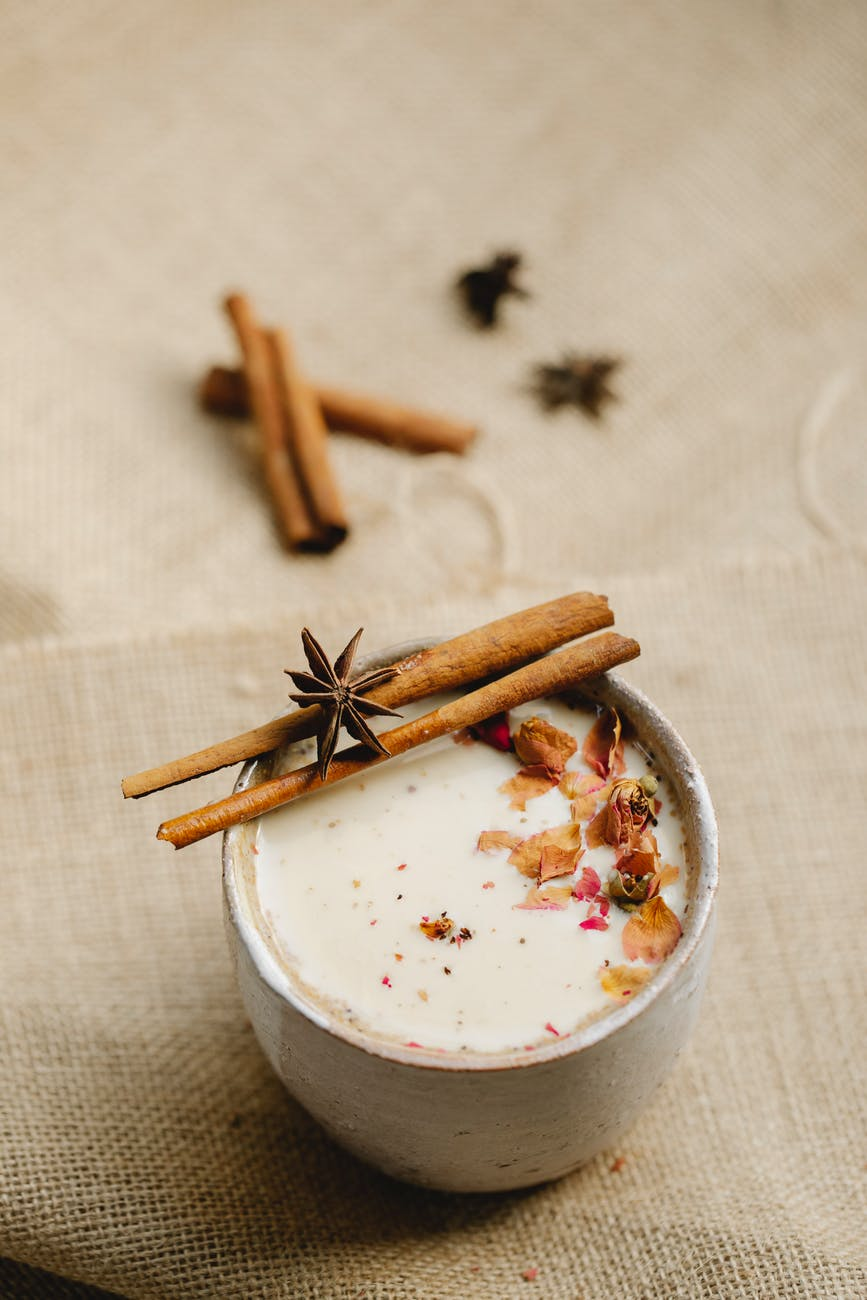 ceramic cup of chai tea with cinnamon and star anise on linen fabric
